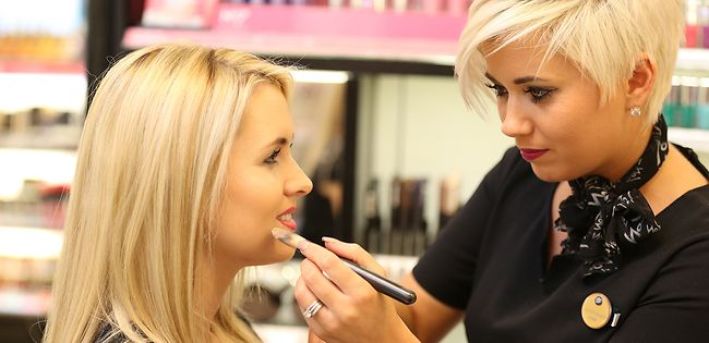 Member of Boots staff giving woman a makeover